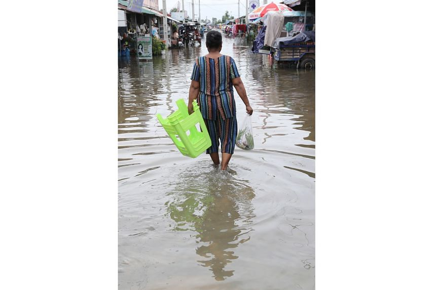 A flooded street on the outskirts of Phnom Penh, Cambodia, yesterday. Floods have displaced thousands of people in western Cambodia.