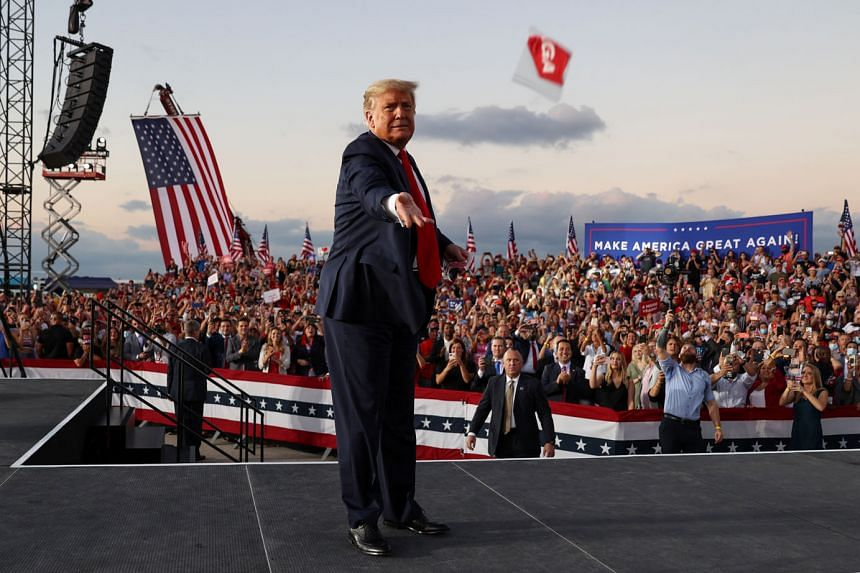US President Donald Trump tossing out face masks to the crowd at a campaign rally, his first since he announced his Covid-19 diagnosis, at an airport in Sanford, Florida, on Monday. The event is the first of six planned for this week. He is also expected