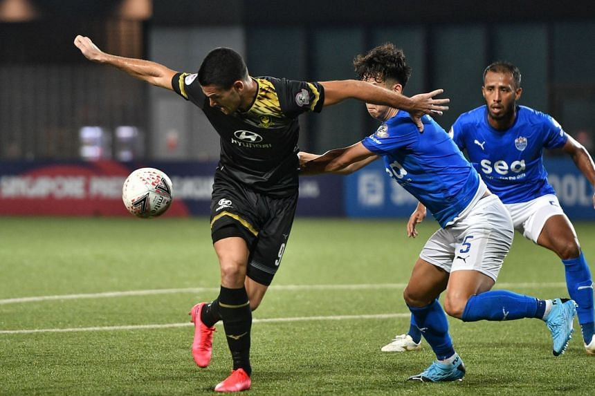 Tampines Rovers' Boris Kopitovic shields the ball against Lion City Sailors players on March 18, 2020.
