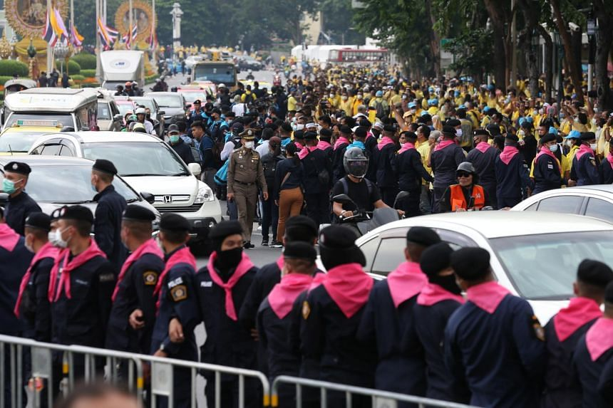 Thai police standing guard while royalist supporters (in yellow shirt) faced with the anti-government protesters in Bangkok, on Oct 14, 2020.