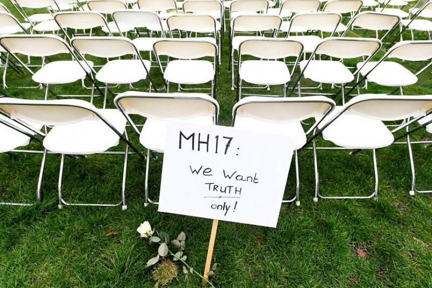 A protest sign stands as family members of victims of the MH17 crash lined up empty chairs for each seat on the plane.