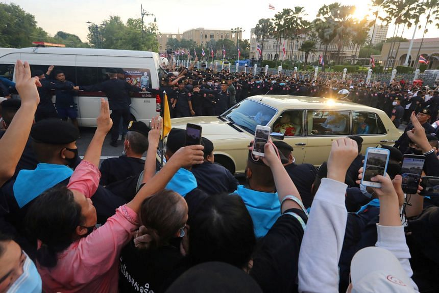 The royal motorcade with Thai Queen Suthida and Prince Dipangkorn driving past anti-government protesters in Bangkok on Oct 14, 2020.