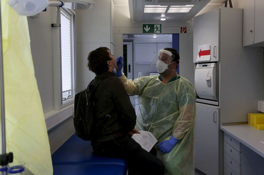 A health worker administering a Covid-19 swab test on a traveller in Berlin on Monday. Germany, where infections jumped by 4,122 on Tuesday to 329,453 in total, has secured nine million so-called antigen tests per month that can deliver a result in m