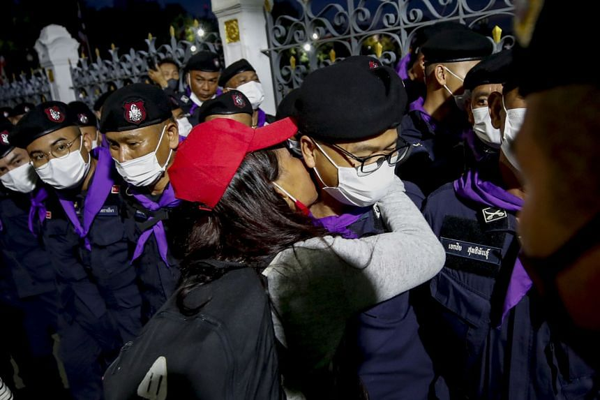 A protester kissing a Royal Thai Police officer guarding Government House in Bangkok during yesterday's mass protest. Pro-democracy demonstrators lighting up their mobile phones as they gathered outside Government House in Bangkok yesterday. They wan