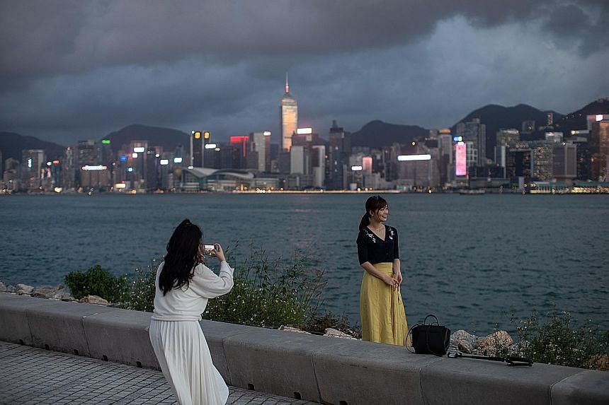Women snapping photos at the West Kowloon Waterfront Promenade in Hong Kong last week. Transport Minister Ong Ye Kung yesterday called the move to set up an air travel bubble between Singapore and Hong Kong a small but significant step for the two av