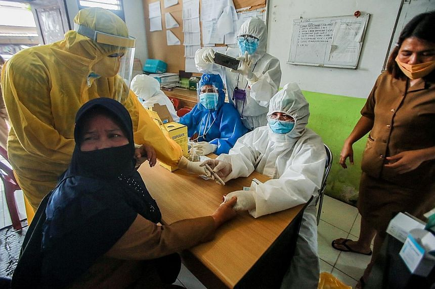 A woman having her blood sample taken for coronavirus testing in Medan, North Sumatra, this week. The Indonesian government has blamed the surge in Covid-19 infections on people's failure to comply with health protocols such as wearing masks and soci