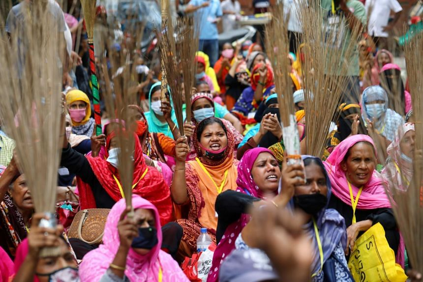 Garment workers shout slogans while holding brooms during a protest demanding their due wages in Dhaka on Sept 7, 2020.