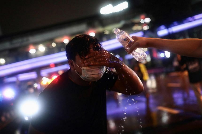 A protester getting his face washed after Thai police deployed water cannon, allegedly laced with a chemical mixture, during a demonstration in Bangkok on Oct 16, 2020.