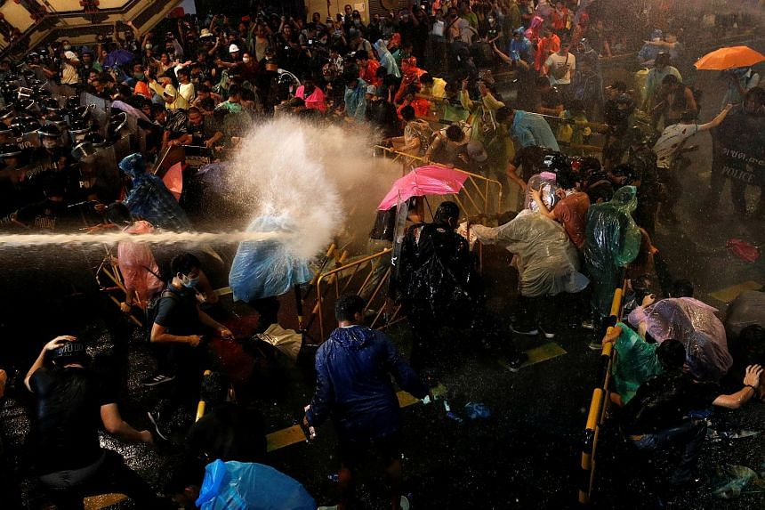 A pro-democracy protester getting hit by water cannon during a demonstration in Bangkok on Oct 16, 2020.