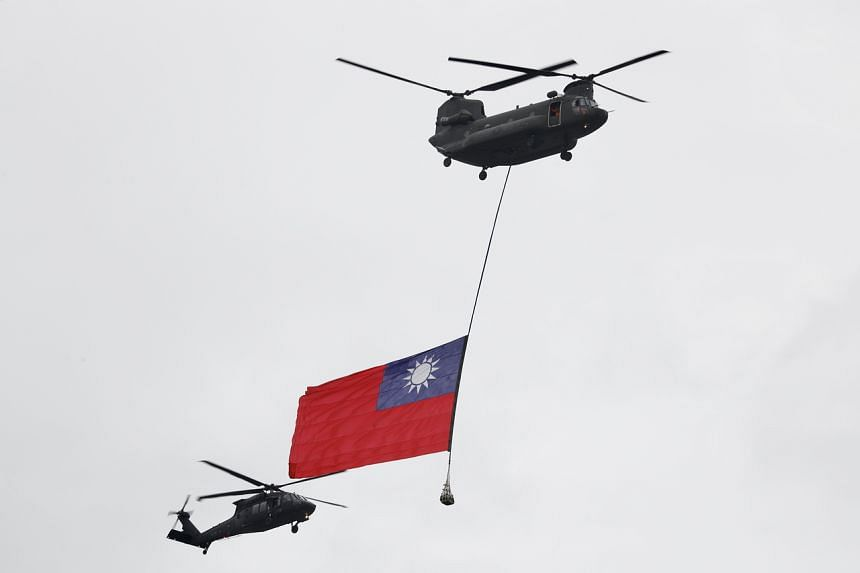 A military helicopter flies with Taiwan's national flag in Taipei on Oct 10, 2020.