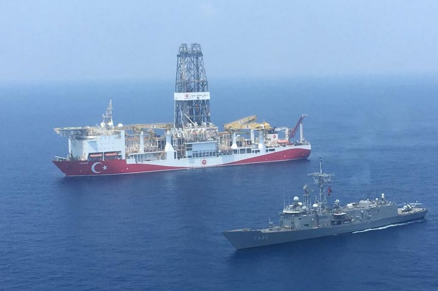 A photo taken on July 9, 2019, shows a Turkish Navy warship next to Turkey's drilling ship in the eastern Mediterranean near Cyprus.