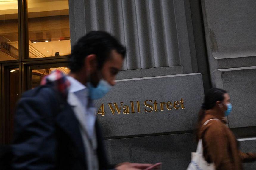 People walk by the New York Stock Exchange in lower Manhattan.