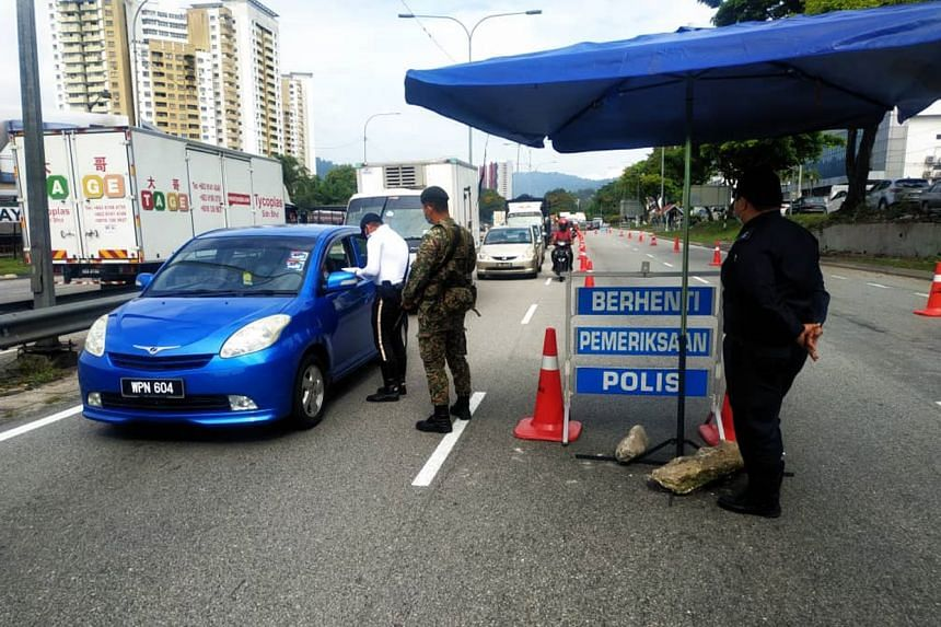 Malaysian police and army personnel at one of the 93 roadblocks set up around the Klang Valley under the conditional movement control order, on Oct 14, 2020.