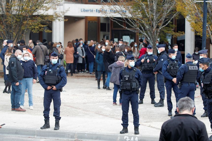 People gather in front of the Bois d'Aulne college after the attack in the Paris suburb of Conflans St Honorine, France, on Oct 17, 2020.