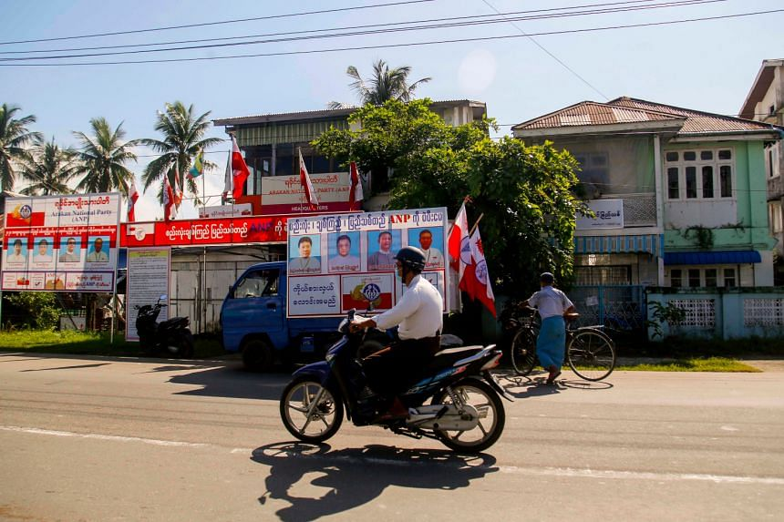 A motorist rides past the campaign signboards of the Arakan National Party in Sittwe, Rakhine, on Oct 14, 2020.