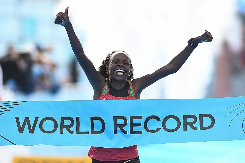 Kenyan Peres Jepchirchir is delighted as she crosses the finishing line in a world record time of 1:05:16.
