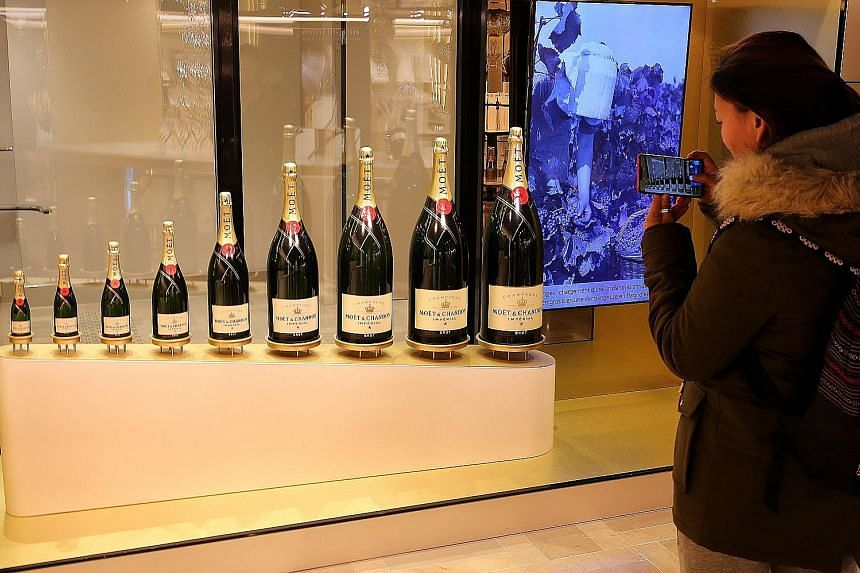A tourist taking a photo of champagne bottles on the Champagne Avenue in Epernay, north-eastern France, last year. The consumption of champagne has dipped sharply because of the pandemic.