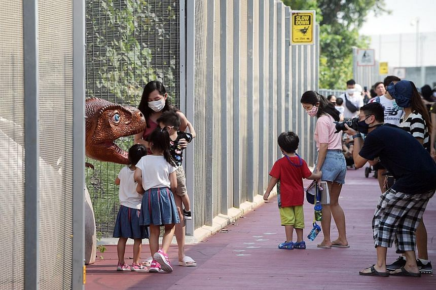 Visitors at the Changi Jurassic Mile between Terminal 4 and the entrance to East Coast Park yesterday morning. The outdoor display of more than 20 dinosaur models has been drawing crowds since it opened last week. Visitors must now reserve a slot on