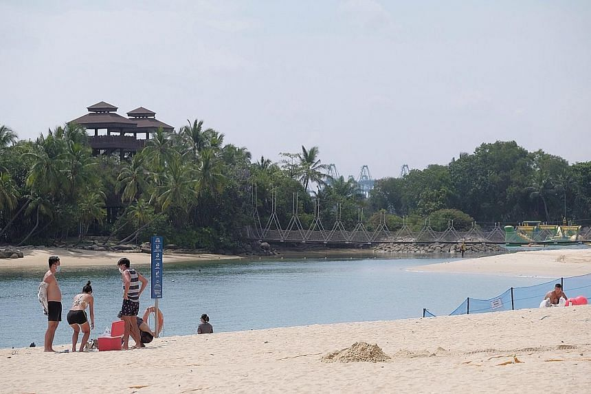 At Palawan Beach yesterday, guests were issued wristbands for admission after they presented their confirmation e-mail for verification. Beachgoers yesterday at Palawan Beach on Sentosa had plenty of space to themselves, with the roll-out of an onlin