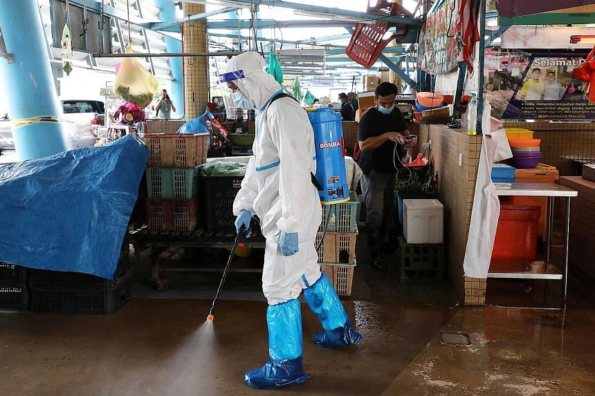 Above: A worker wearing personal protective equipment spraying disinfectant at a market in Putrajaya, Malaysia, last Thursday. Left: Some stores in Malaysia's iconic Suria KLCC shopping mall are closing earlier than usual as customers stay home amid