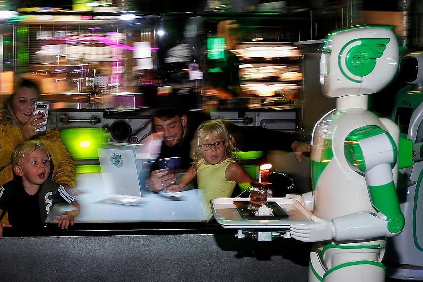 A robot serving a birthday cake to restaurant patrons in Britain earlier this month amid the coronavirus pandemic. An OriHime-D robot developed by Ory Laboratory at the Nippon Telegraph and Telephone headquarters in Tokyo earlier this month. A robot