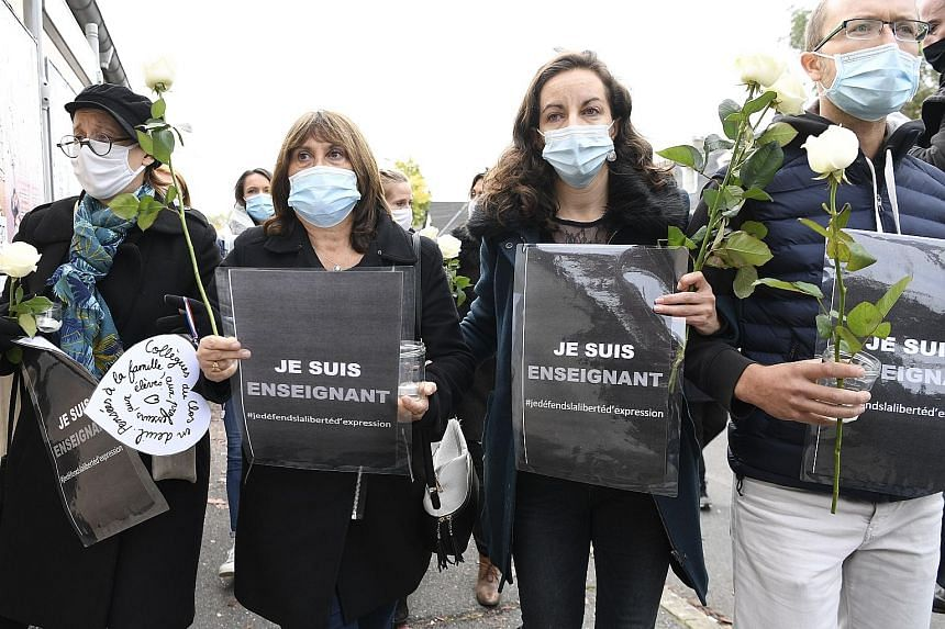 """People holding signs that read """"I am a teacher - freedom of speech"""" outside a school in Conflans-Saint-Honorine yesterday, a day after the fatal incident. Some parents had complained after the teacher, Mr Samuel Paty, showed his students cartoons of"""