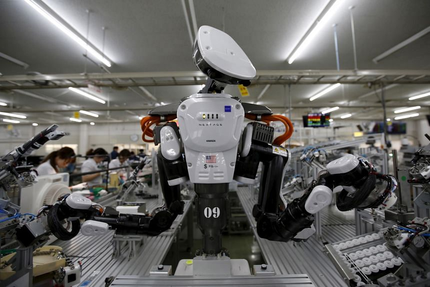 A robot working at a factory of Glory, a manufacturer of automatic change dispensers, in Japan in 2015.