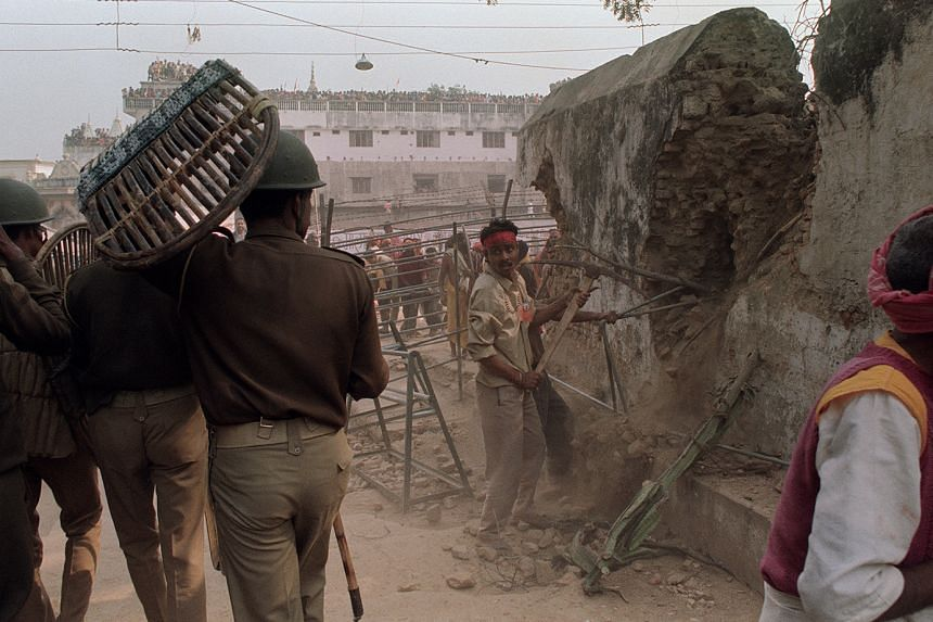 "A photo taken in 1992 showing Hindu nationalists demolishing the wall of the 16th-century Babri Masjid in Ayodhya city in the presence of riot police. The Indian Supreme Court last year called the demolition of the mosque an ""egregious violation of"