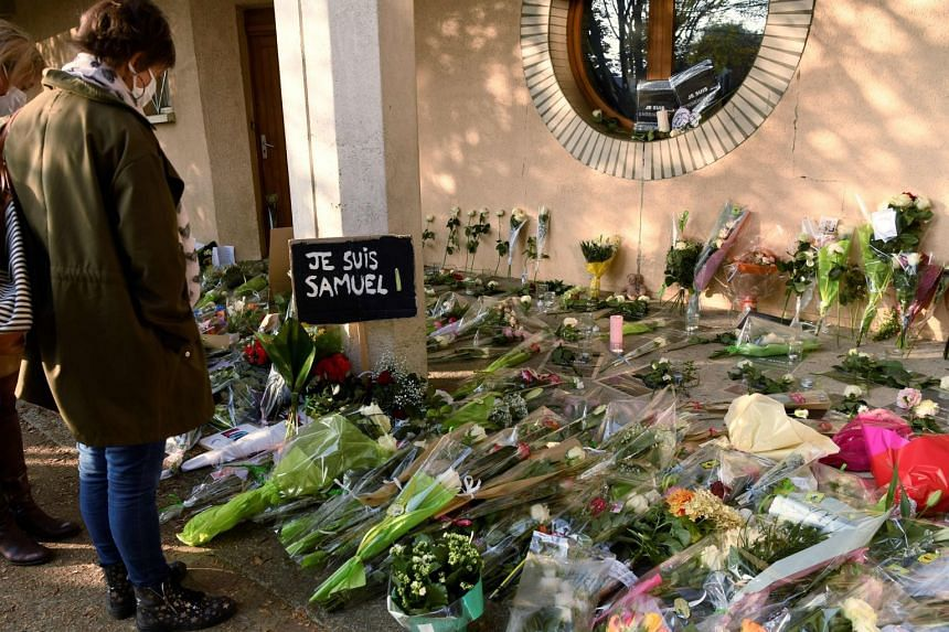 People stand near flowers and a placard reading 'I am Samuel' at the entrance of a middle school in France's Conflans-Sainte-Honorine, on Oct 17, 2020.