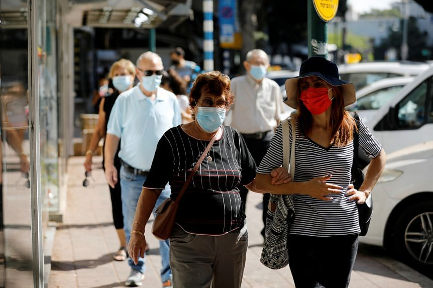 People walking down a street in Ramat Gan, Israel, after the country began easing Covid-19 measures, on Oct 18, 2020.