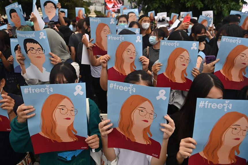 """Protesters holding up posters of Student Union of Thailand spokesperson Panusaya """"Rung"""" Sithijirawattanakul during a demonstration in Bangkok on Oct 18, 2020."""