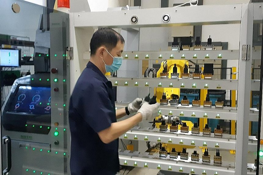 An employee with a machine that makes mould inserts at Koei Tool, whose automation of production processes has lifted productivity.