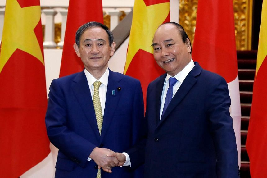 Japan's Prime Minister Yoshihide Suga (left) shakes hands with Vietnam's Prime Minister Nguyen Xuan Phuc during an official visit at the Government Office in Hanoi on Oct 19, 2020.