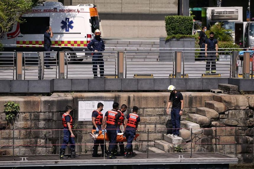 SCDF officers moving the body of a man found in the waters off the Promontory on Oct 19, 2020.