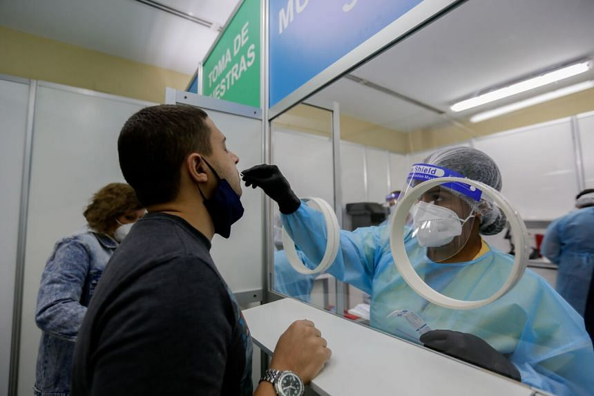 A health worker takes a swab sample at Tocumen International Airport in Panama on Oct 12, 2020.