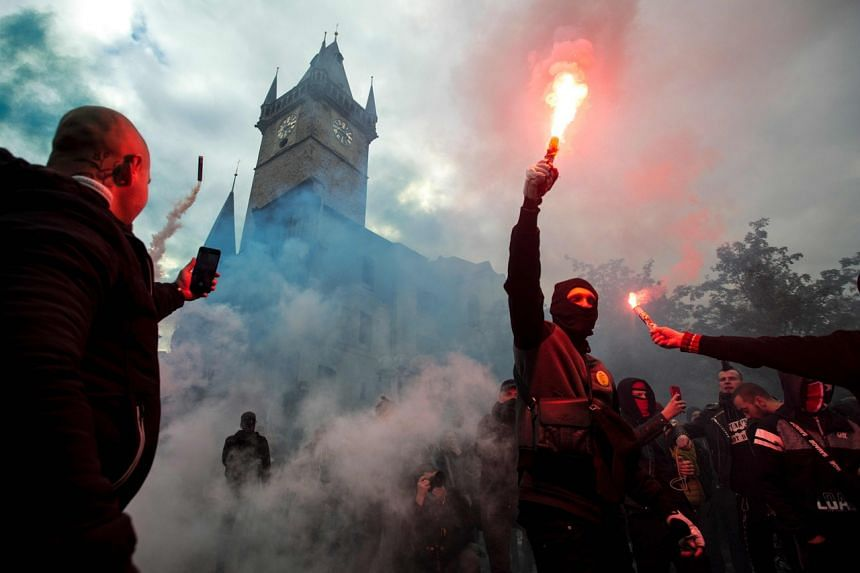 Protestors light flares at the Old Town Square in Prague on Oct 18, 2020.