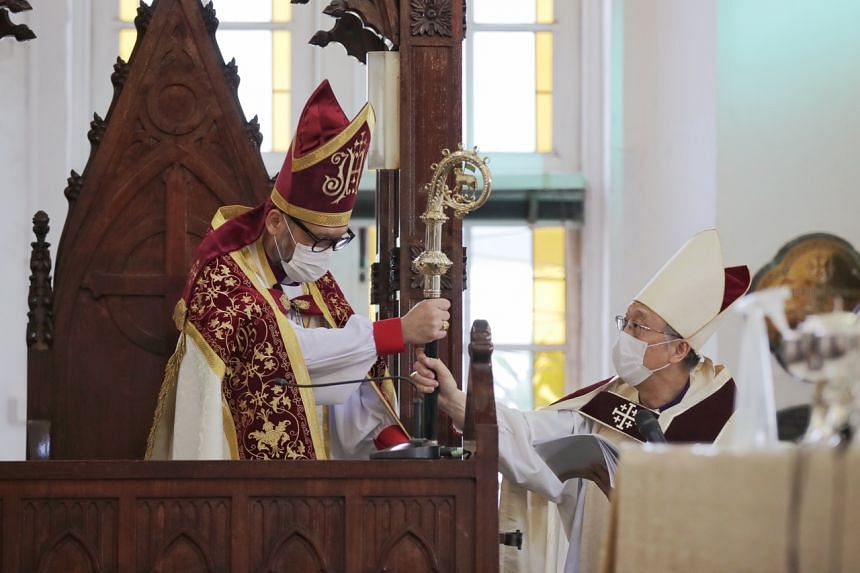 Reverend Canon Dr Titus Chung (left) receives the Diocesan Crosier, or Bishop's staff, from Right Reverend John Chew at Saint Andrew's Cathedral on Oct 18, 2020.