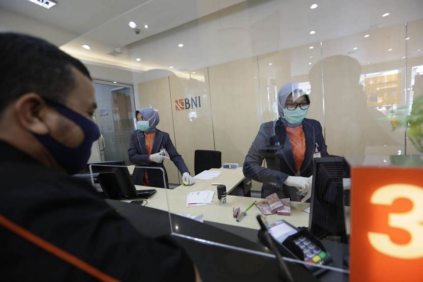 A Bank Negara Indonesia (BNI) teller serving a customer in Banda Aceh in May. Last Tuesday, the Indonesian government announced that it would merge the syariah units of three state-owned lenders, including BNI, to form the country's seventh-largest