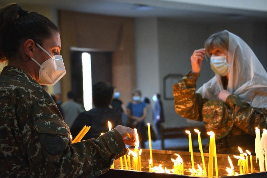 Armenians lighting candles in a church in Yerevan last Saturday for their countrymen killed during fighting over the breakaway region of Nagorno-Karabakh. The truce agreed to last Saturday came into force at midnight after a week-old Russian-brokered