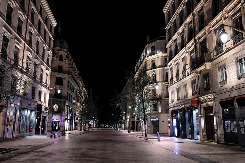 A deserted street in Lyon, France, last Saturday, after a month-long night-time curfew was put in place in nine cities in the country. Those venturing outside risk a fine unless they can show good reason to be out and about. PHOTO: AGENCE FRANCE-PRES