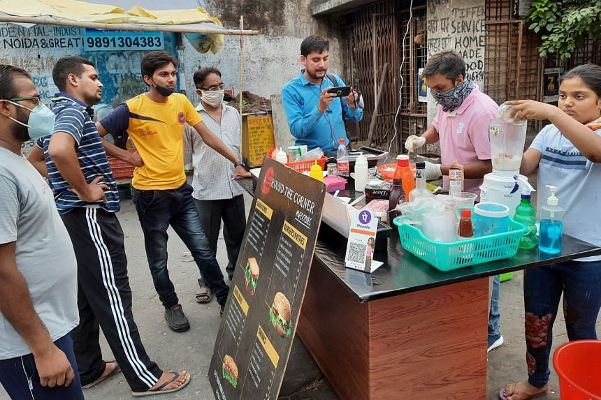 Mr Ravi Kant at his food stall in Noida, which sells mostly burgers, sandwiches and beverages. He saw a surge in customers after a news agency tweeted about him and his stall. ST PHOTO: DEBARSHI DASGUPTA