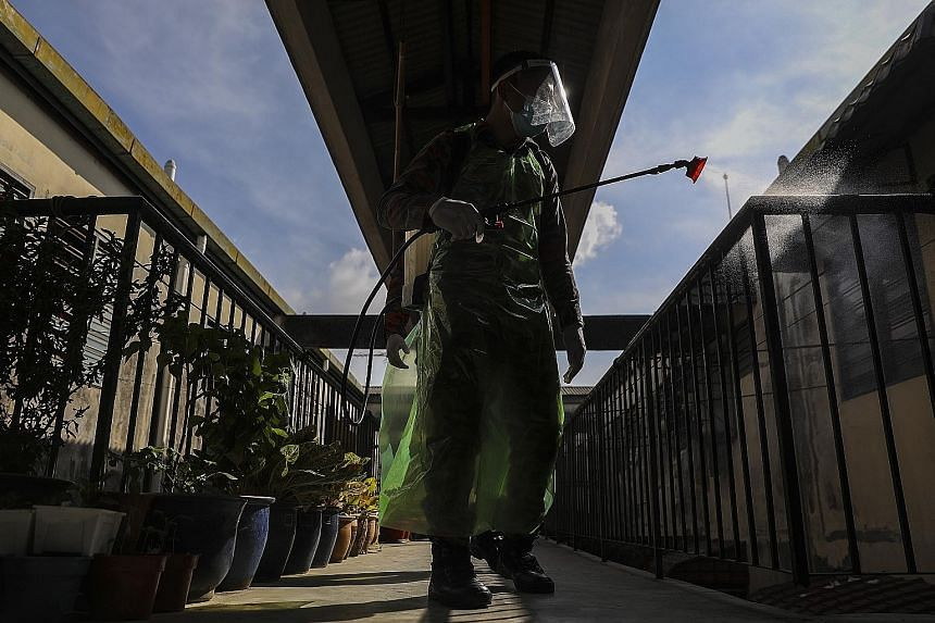 A Malaysian Fire and Rescue Department officer sanitising an area outside a block of apartments in Shah Alam, Selangor, yesterday. The country recorded 865 cases yesterday, the third consecutive day when daily infections were above 800. The governmen