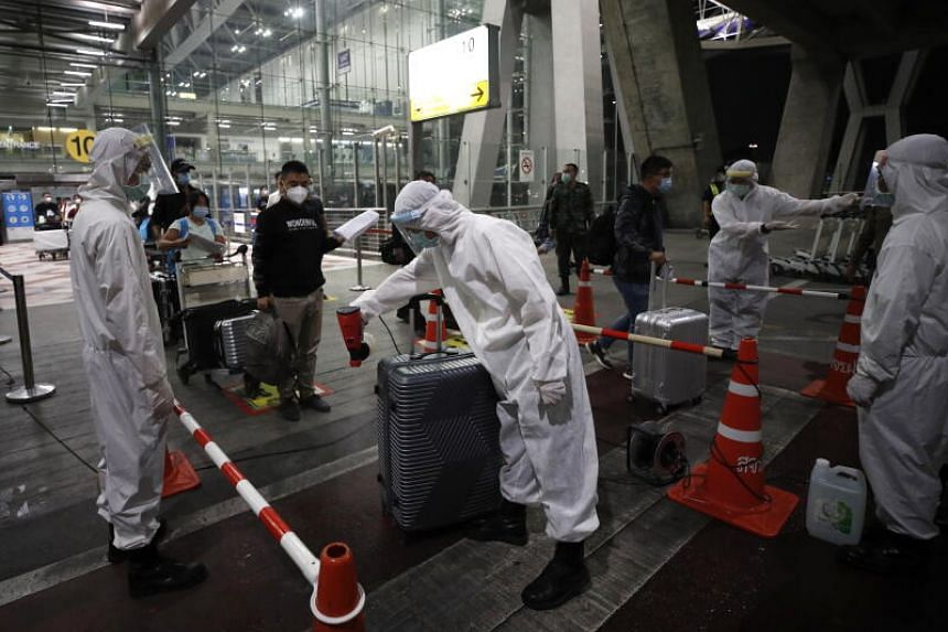 Masked tourists exiting the airport, with officials in full protective equipment spraying their luggage with disinfectant.