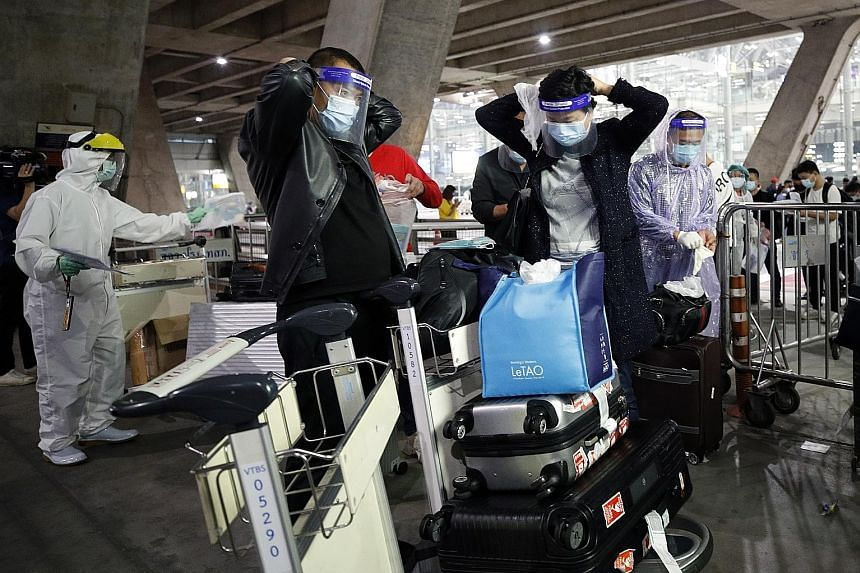 Chinese tourists in raincoats and face shields boarding a bus at Suvarnabhumi Airport heading to their hotels for the mandatory 14-day quarantine on Tuesday. New tourist arrivals in Thailand must quarantine for two weeks and test negative three times