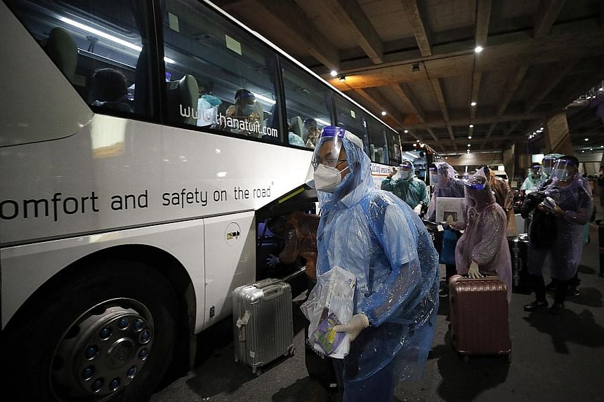 Chinese tourists putting on raincoats and face shields as part of Thailand's coronavirus pandemic restrictions at Suvarnabhumi Airport on Tuesday.
