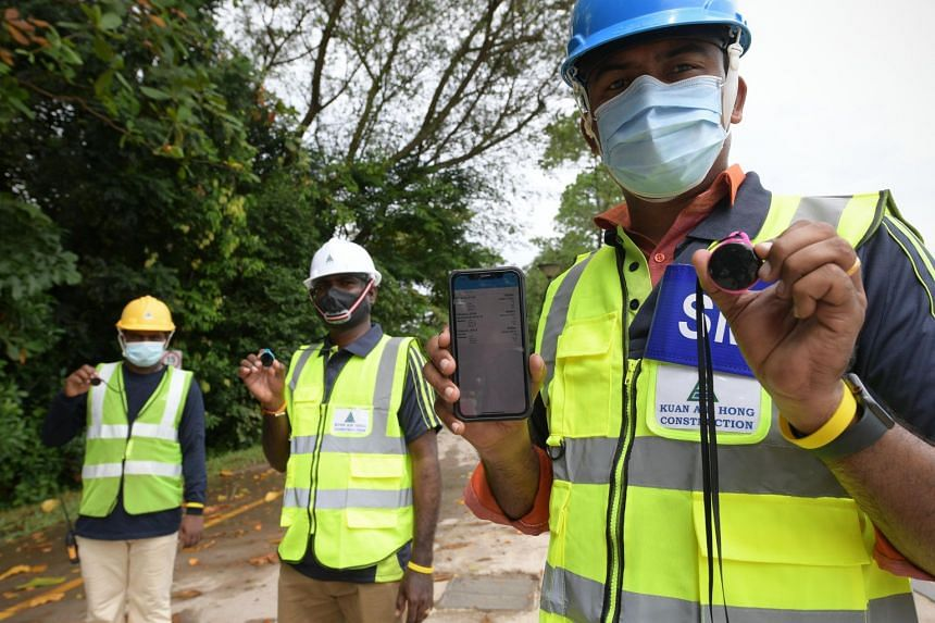 Migrant workers hold a device that encourages workers to keep at a safe distance from one another through an alarm.
