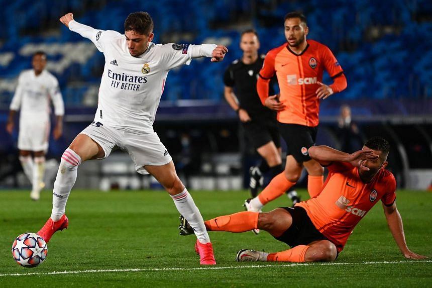 Real Madrid's Federico Valverde (left) challenges Shakhtar Donetsk defender Davit Khocholava.
