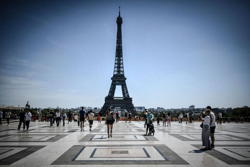 Tourists visit the Esplanade des Droits de l'Homme in Paris, with the Eiffel tower in the background.