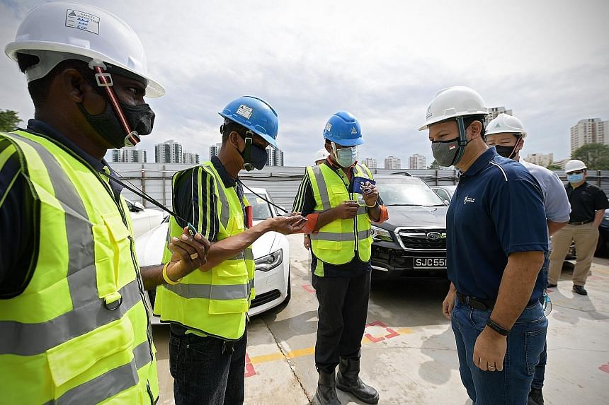 Senior Minister of State for Manpower Zaqy Mohamad (right) speaking with migrant workers while visiting a construction worksite at the Chinese Garden yesterday. As part of safe management measures amid the coronavirus pandemic, the workers each wear