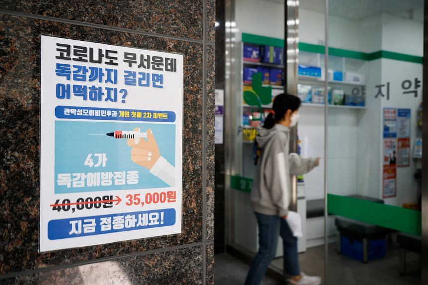 A woman walks past a poster encouraging people to get an influenza vaccine in Seoul, on Oct 23, 2020.